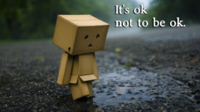 """its okay to not be okay"" cardboard man on rainy day"
