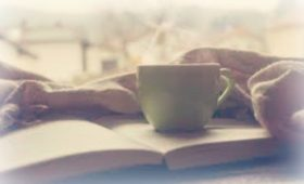 Coffee cup and an open book in the morning