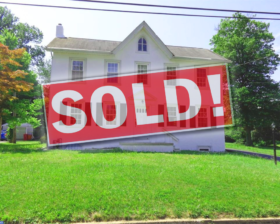 """Audubon house on a green hill with the word """"Sold!"""" accross the front."""