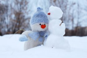 Two snowmen in winter snowpile