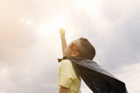young child imagining he is superhero with flying powers